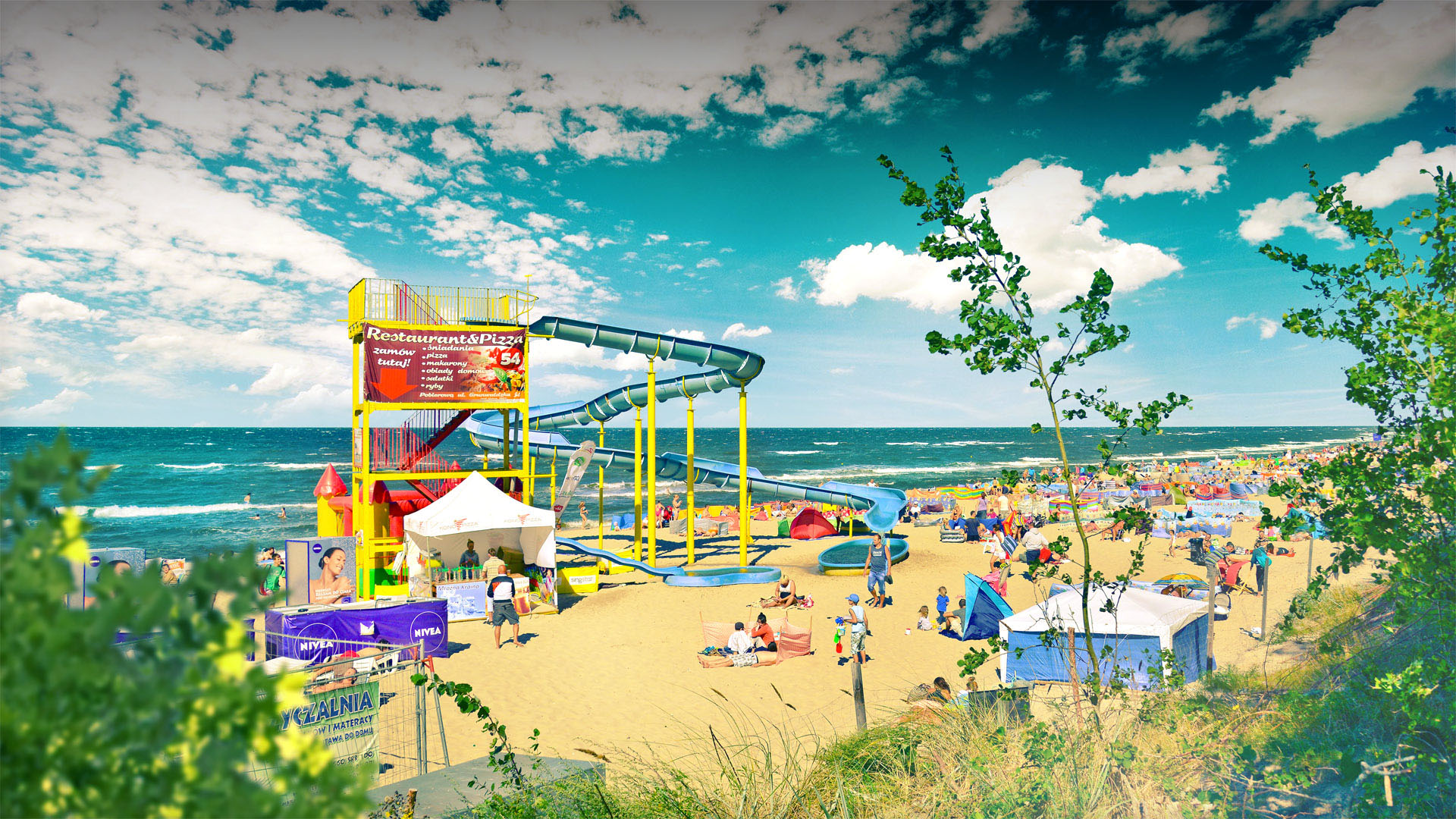 Słoneczny dzień, plaża pełna turystów, zjeżdżalnia wodna.